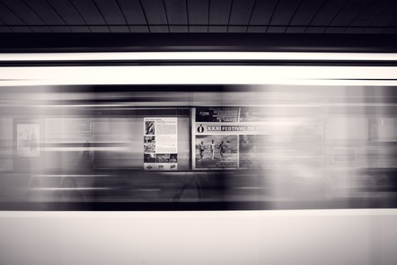 Blurred subway train in motion, with a visible advert in the background.