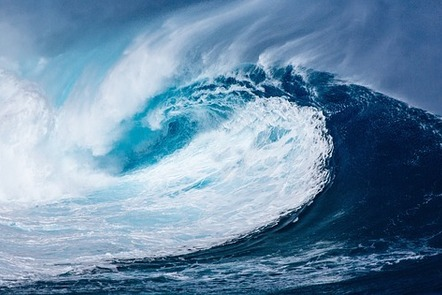 Crest of a large sea wave crashing down on the ocean