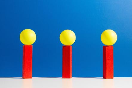 Three yellow balls sitting upon three red plinths