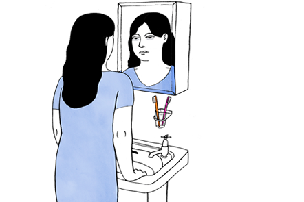 A woman holding onto a bathroom sink. She is looking at her reflection in the mirror.