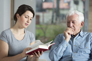 Supporting people living with long-term conditions: a woman reads a book to a man