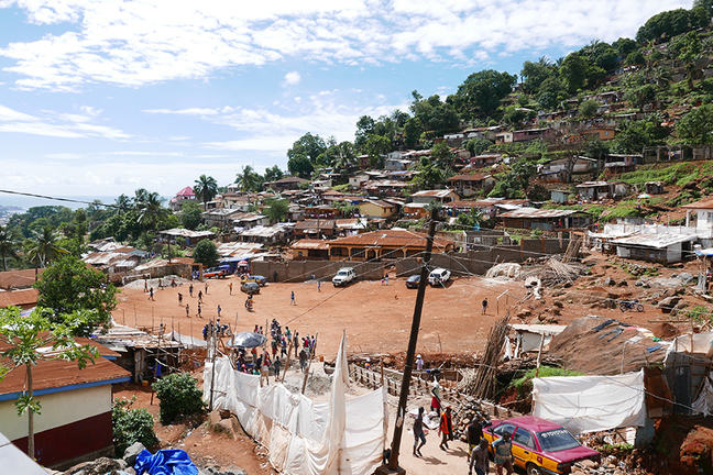 Image of a hillside settlement with a playing field in the centre ground, taxi and walkway in the foreground, and houses with corrugated iron roofs in the background.