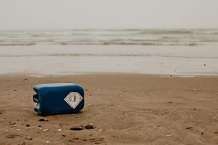 Blue chemical drum washed up on a beach