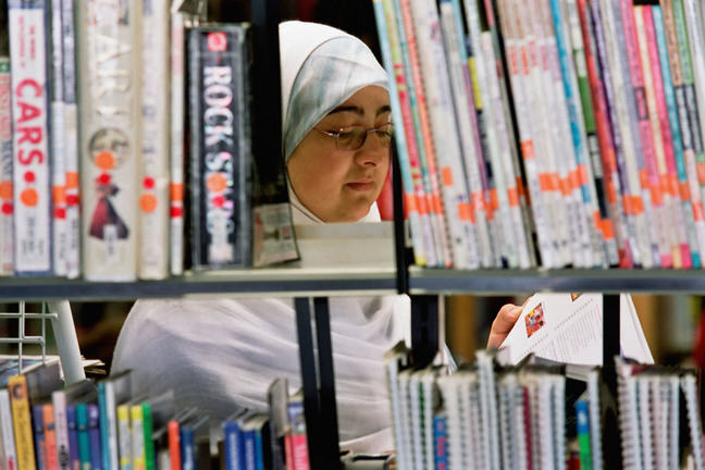 woman in hijab reading in library
