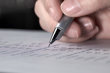 Pen hovering over a piece of paper ready to start writing