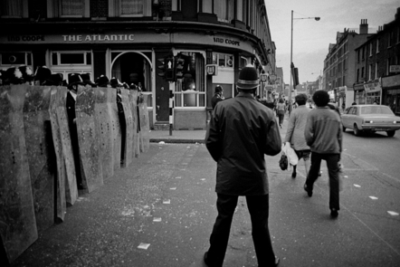 A photograph of a line of police officers in riot gear standing in front of The Atlantic pub in Brixton. Traffic and pedestrians pass by on the right hand side