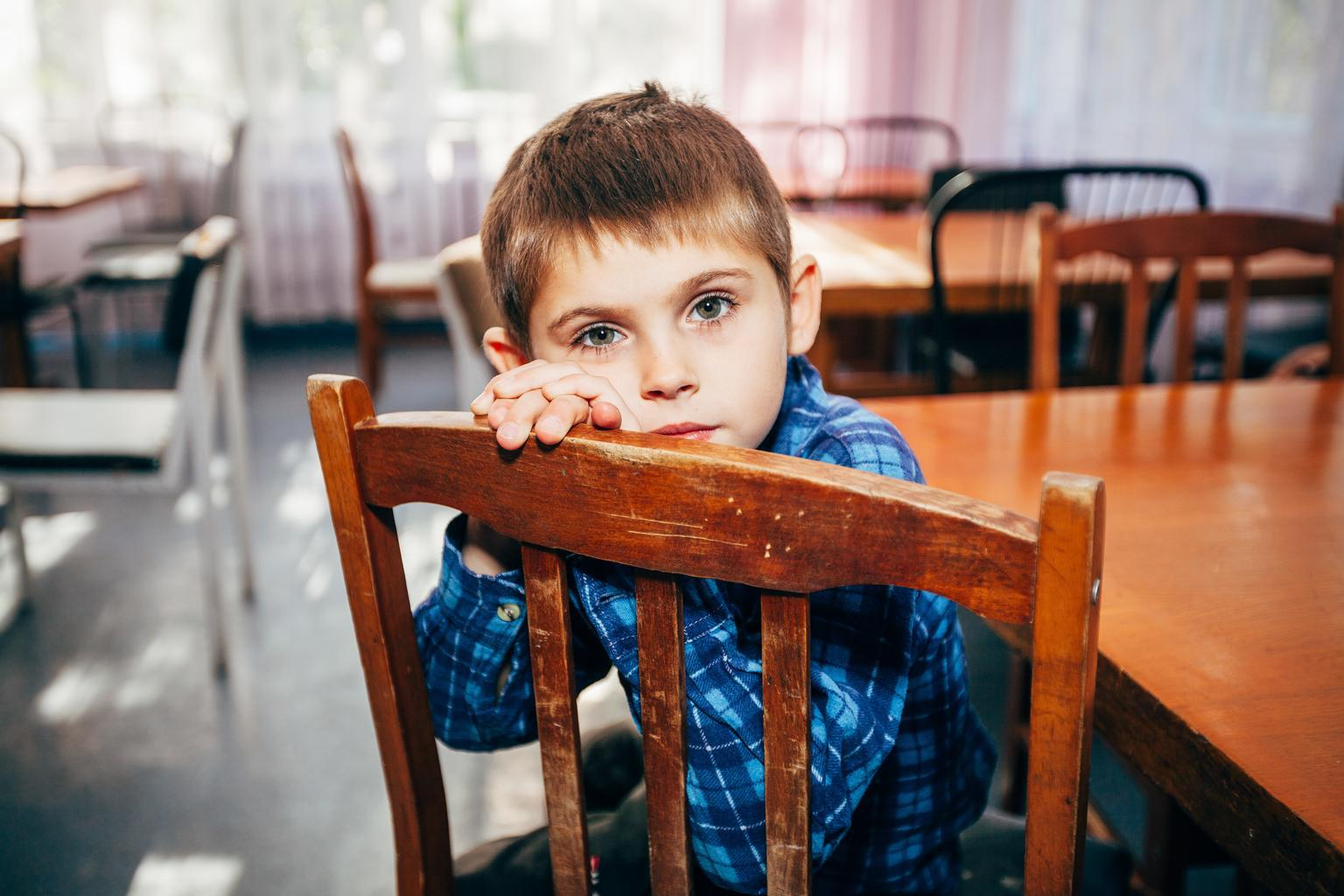A young boy sits facing the back of a wooden chair with his hands resting on the top and his cheek resting on his hands. He is wearing a blue shirt. The room he is in has many tables and chairs, all mismatched.
