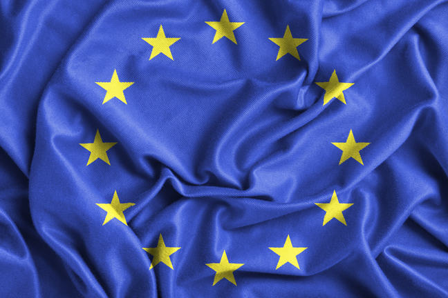 A close up of the European Union blue flag with 12 yellow stars arrranged in a circle