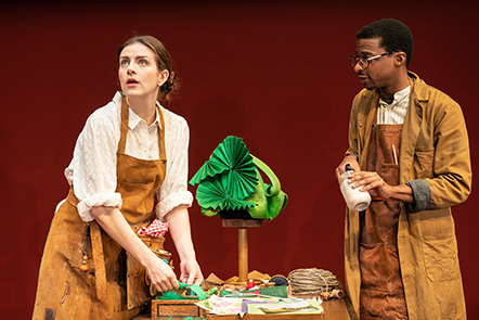 Far Away at the Donmar Warehouse. Aisling Loftus stands to the left of the image looking off into the distance. Simon Manyonda stands to the right of the picture holding a tin of paint.