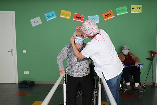 A social worker puts a protective mask on an elderly woman at a nursing home, during the coronavirus disease (COVID-19) outbreak.