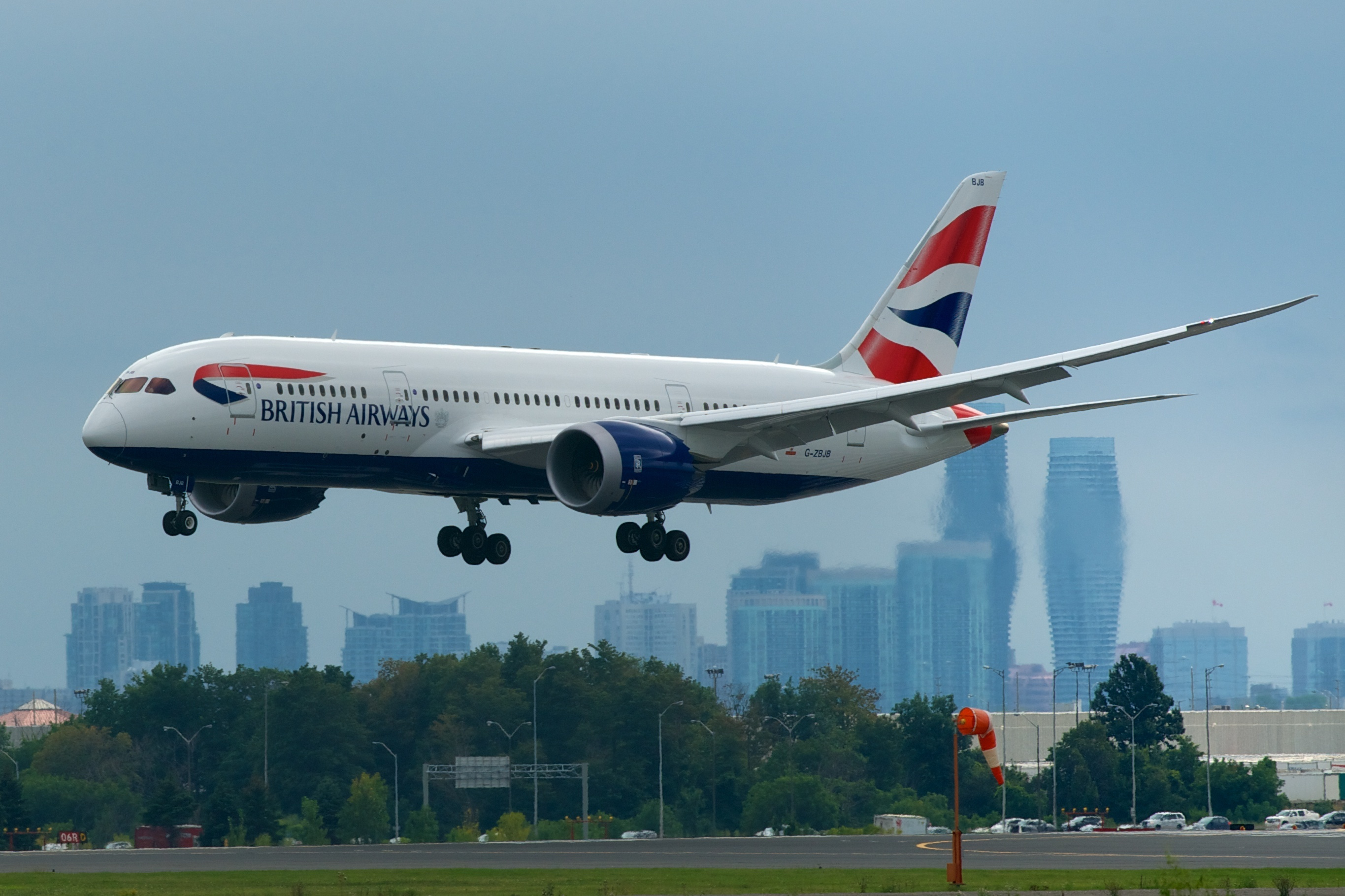 First intercontinental flight of a British Airways Boeing 787-8 about to touch down, Toronto-Pearson Airport with City Centre Mississauga looming in the background.