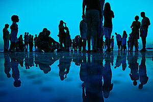 Group of people standing by the ocean, their reflections mirrored in the water below