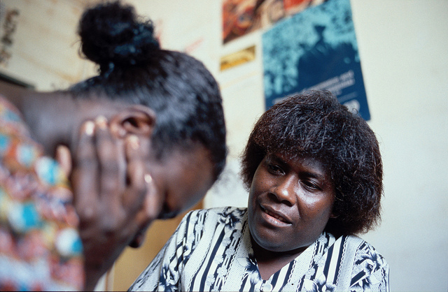 A distraught woman with her head in her hands is being counselled by another woman.