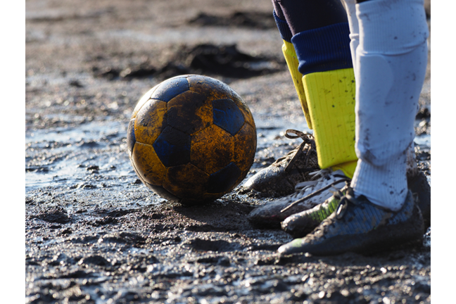 Soccer ball on a muddy field with the feet of two opposing players standing beside it