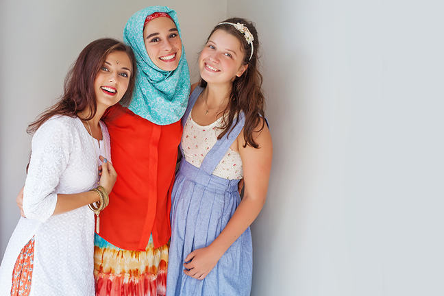 three young women of different faiths posing for a photo