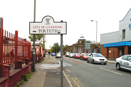 A photograph of a street in Toxteth including a sign that reads 'City of Liverpool: Toxteth'. Cars are parked on either side of the road