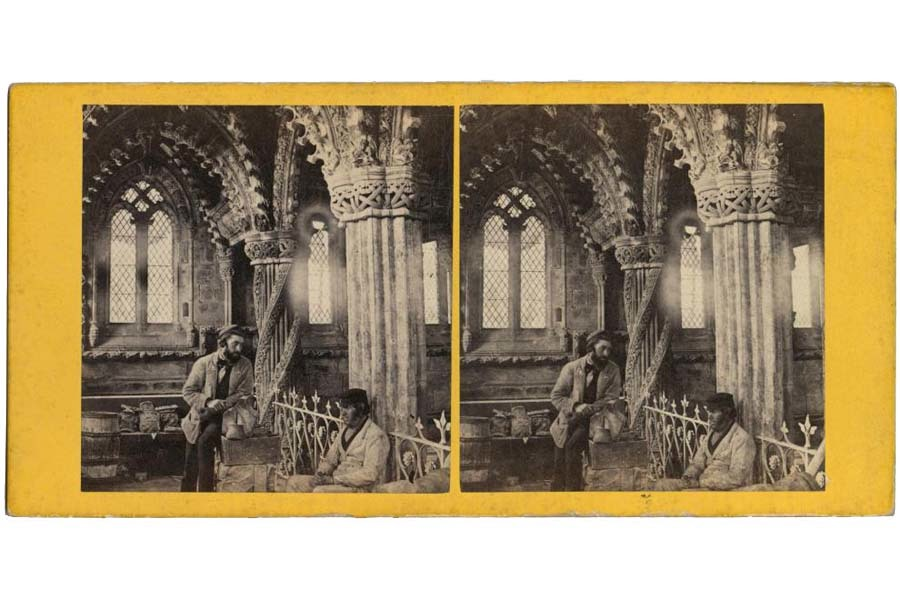 Interior of The Lady Chapel, Roslyn, showing two men, one standing and one seated, with intricate carved pillars behind.