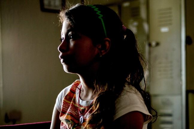 A Central America girl with long dark brown hair put up with a pink elastic and has a green hair band in her hair. She has been photographed in profile (her left side). She is not smiling.