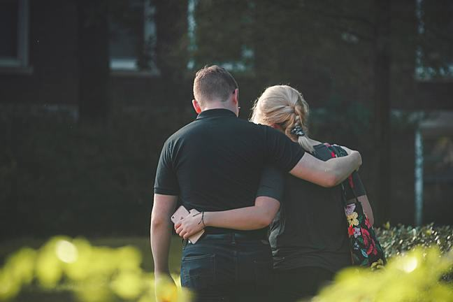 couple walking arm in arm shot from behind