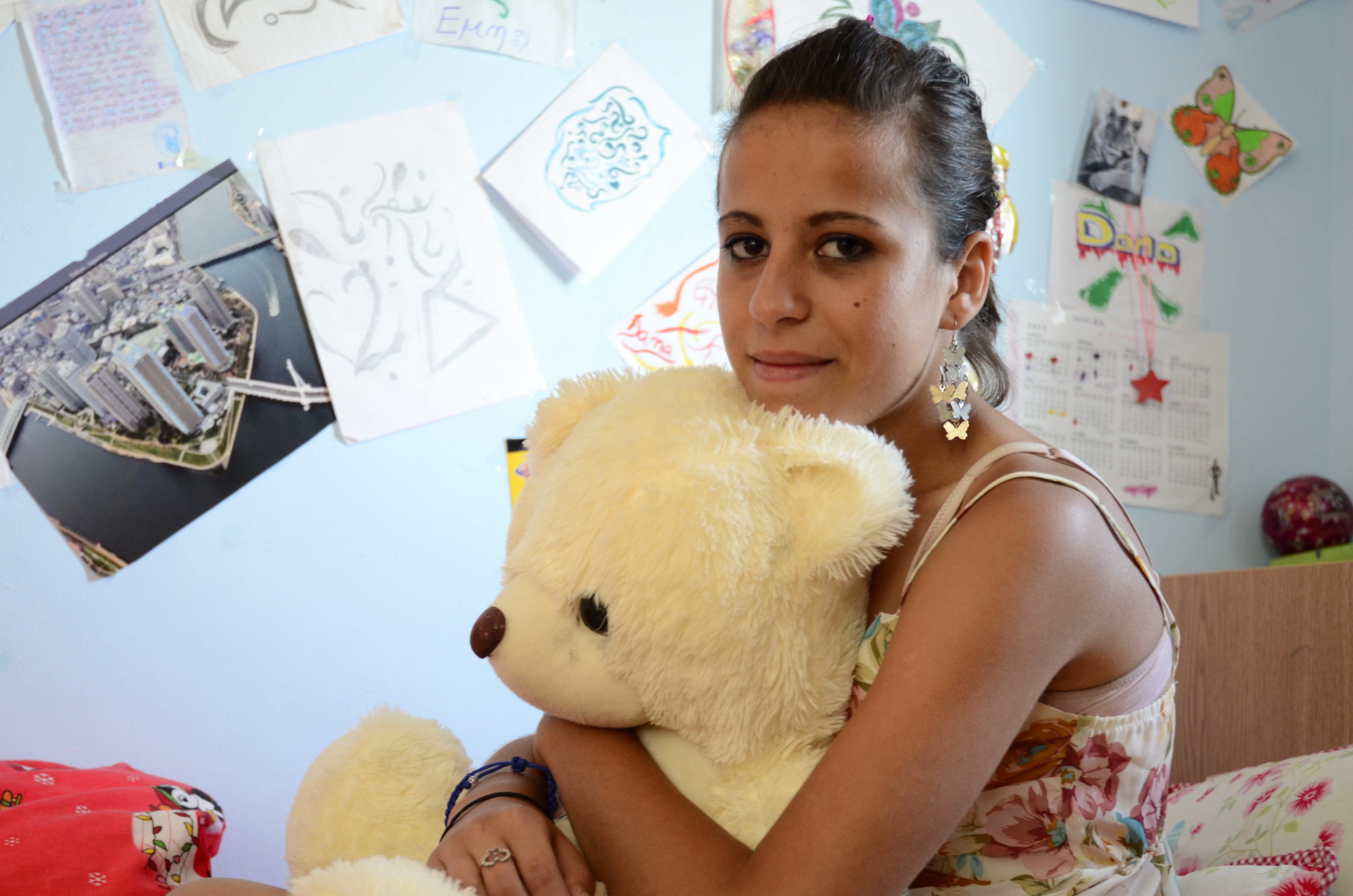 Young woman with sitting on bed clutching a soft toy