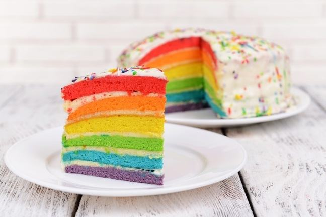 photo of a rainbow cake with a slice cut out of it on a plate by the side of the cake