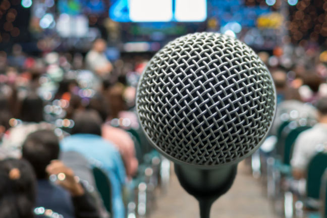 A microphone is shown in front of a blurred conference hall in the background with speakers on the stage and the audience in the background.