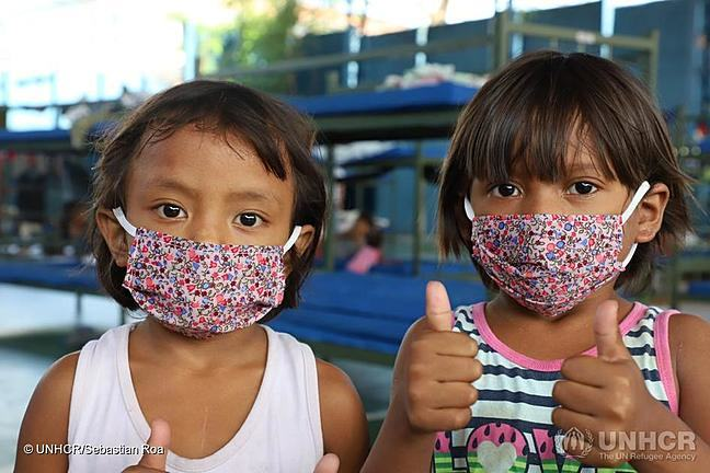 Two young girls wearing masks and with their thumbs up.
