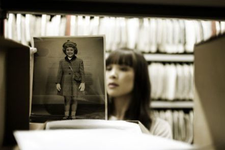 woman in archive looking at a historical photograph of a young girl