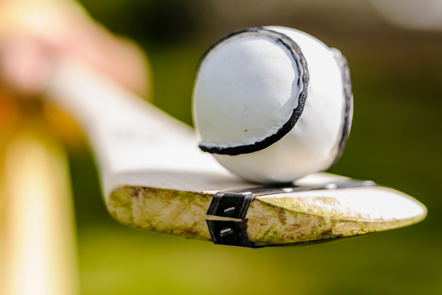 A sliotar (a hard, white leather ball with black stitching) balances on a hurley (an ask stick bound with a curved end)
