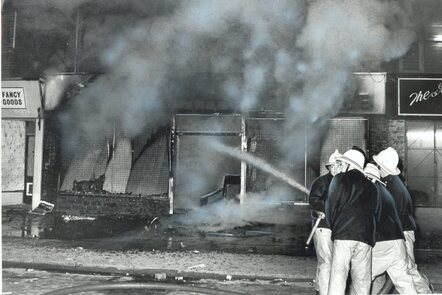 A photograph of firefighters putting out a blaze at a residential address during the riots