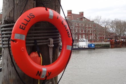 Close up of lifebuoy with Ellis Island in the background