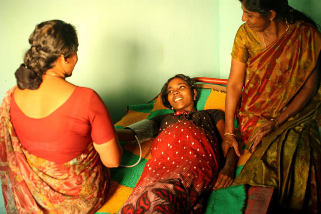 A nurse tends to a female patient lying in bed as a relative looks on.