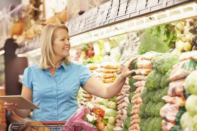 A woman shopping for vegetables in a supermarket holding an electronic tablet.