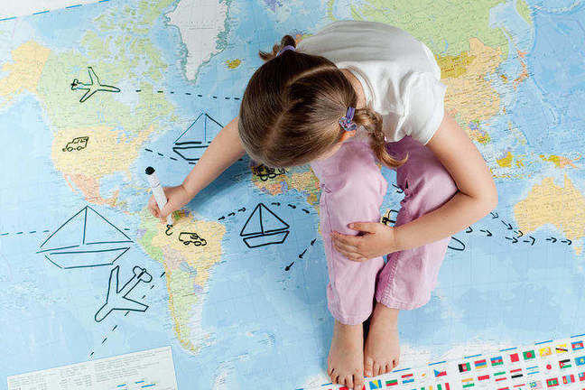 Image of young girl sitting on a map and drawing