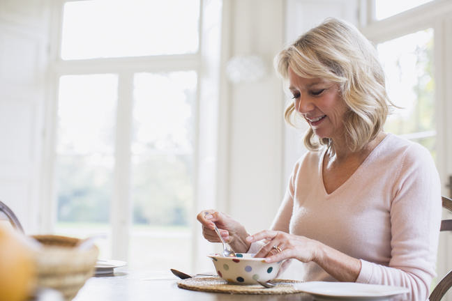 Smiling mature woman eating breakfast