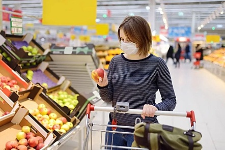 a woman shooping for food wearing a face mask