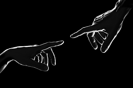 Two hands meeting with a black background