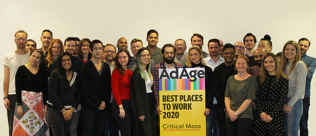 "Some of the Critical Mass team holding a sign that reads ""Ad Age Best Places to Work 2020"""