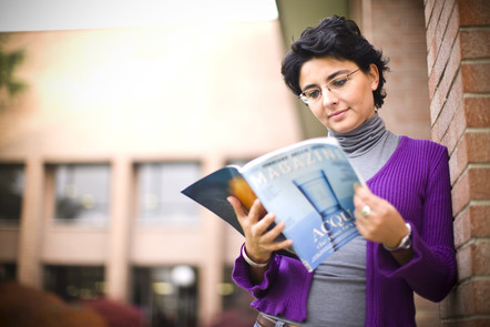 A student leaning on a wall and reading a magazine
