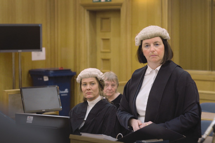 Judges are standing in court. They are wearing traditional wigs and robes.