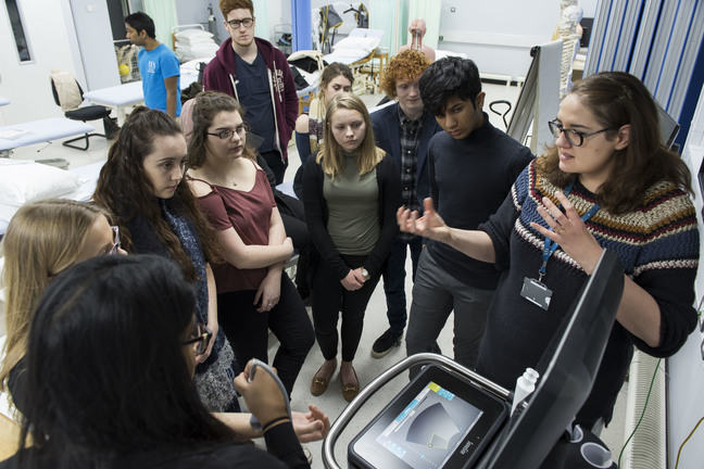 Students gathered around a piece of medical equipment