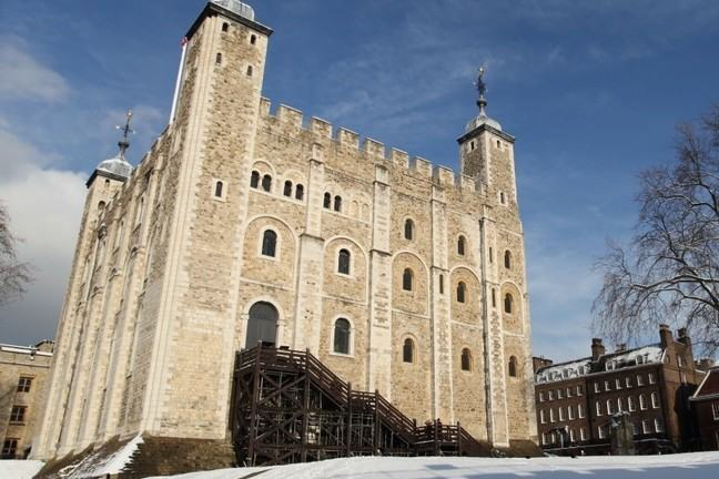 A photograph of the White Tower of the Tower of London. The grounds and rooftops are covered in snow.