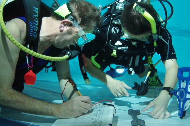 Nautical Archaeology Society trainees learning to recording artefacts underwater.