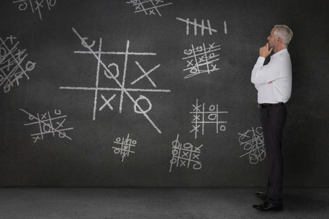 Man looking at tic tac toe games chalked on a blackboard
