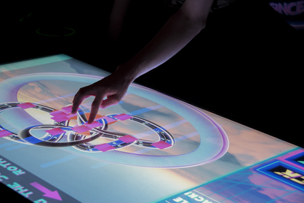 A hand manipulates a touch-screen showing an interactive graphic game.
