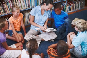 Woman reads picturebook to a group of children sitting in a circle in a library setting. The woman points at the pictures and text while the children look on with apparent interest.