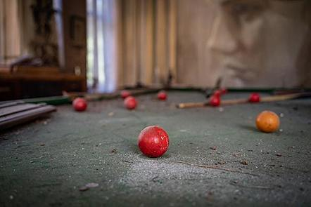 old pool table with balls and cue