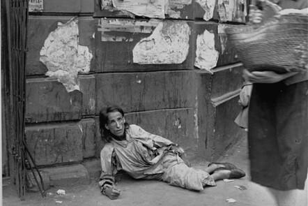 A destitute woman lies on a sidewalk along Nowolipie Street in the Warsaw ghetto.