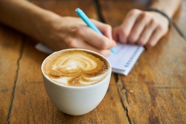 Cup of coffee with someone writing on a notepad in the background