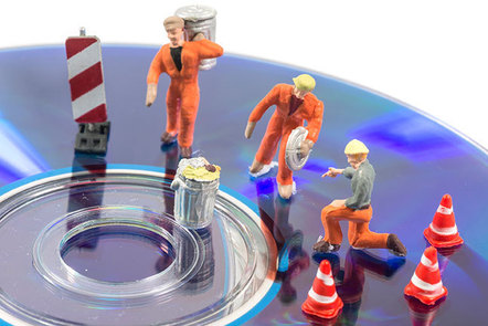 Tiny plastic workmen with dustbins working on a CD. They have tiny plastic cones.